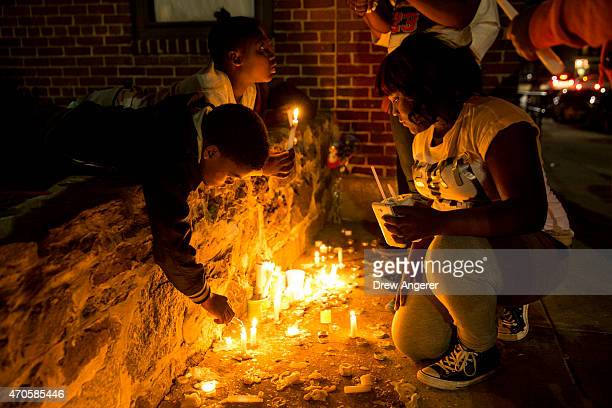 Neighborhood children light candles at a memorial after a march and vigil for Freddie Gray April 21 2015 in Baltimore Maryland Gray died from spinal...