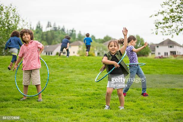 neighborhood children playing together outside - playing tag stock photos and pictures