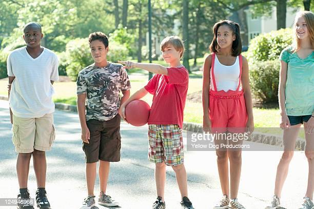 neighborhood kids choosing sides for kickball game - kickball stock photos and pictures