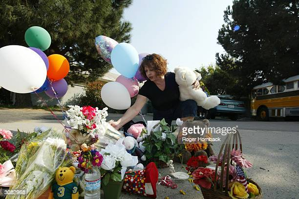 Neighborhood resident Yvonne Medina places items at the memorial in front of the house March 13 2004 in Fresno California According to reports nine...