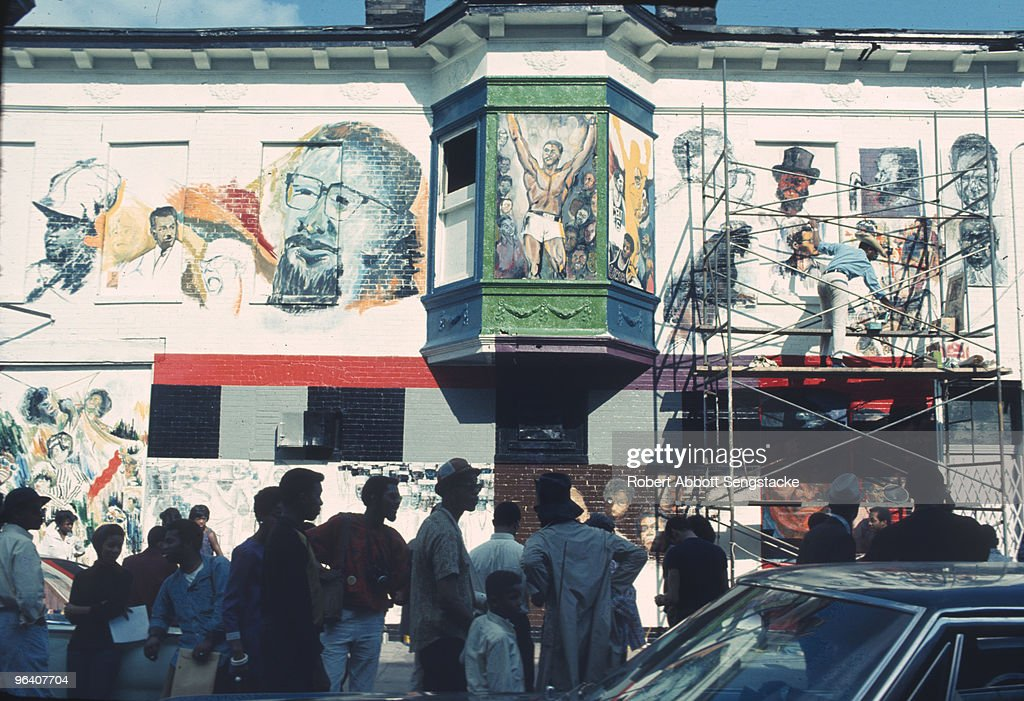 Neighborhood residents and artists gather during the creation of 'The Wall of Respect', a public art project conceived by OBAC (Organization of Black American Culture), Chicago, Illinois, 1967. Painted by a group of African-American artists, the mural was on 43rd and Langley in Chicago's South Side. It depicts images of 'Black Heroes' as positive role models for identity, community formation, and revolutionary action, and was a spur to the public art movement.