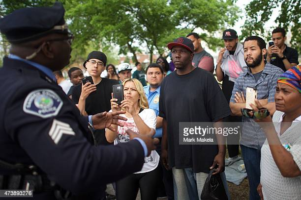 Neighborhood residents film a police officer with their mobile phones while speaking about police mistreatment across the street from where President...