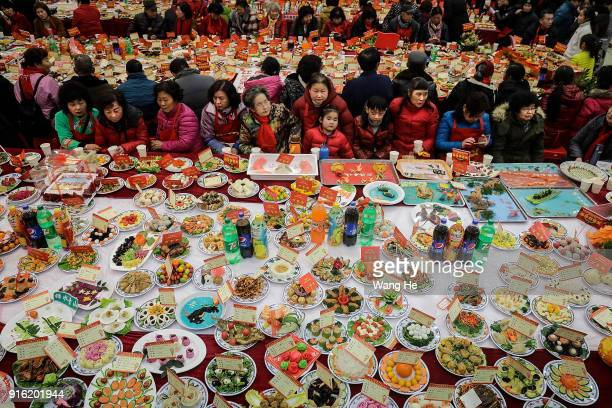 Neighborhood residents sit around a table full of homemade dishes on February 9 2018 in Wuhan Hubei province China Community residents cook thousands...