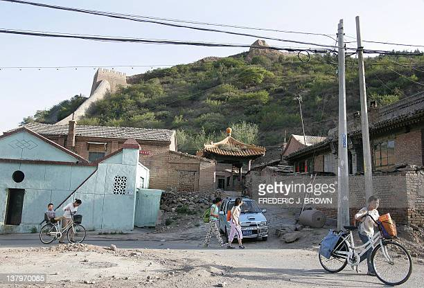 Neighborhood residents walk past the Dajingmen Great Wall which overlooks the historic garrison town of Zhangjiakou 24 May 2006 some 180 kilometers...