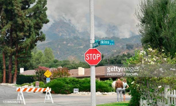 Neighborhood residents watch as the Bobcat Fire burns on hillsides behind homes in Arcadia, California on September 13, 2020 prompting mandatory...