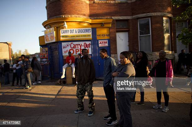 Neighborhood residents watch riot police blockade the street after citywide riots over the death of Freddie Gray on April 28, 2015 in Baltimore,...