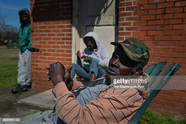 Neighborhood residents Wesley Marshall, L, Alice Douglas, C, and John Johnson, R, relax in the Minnie B. Anderson Homes neighborhood, a dilapidated...