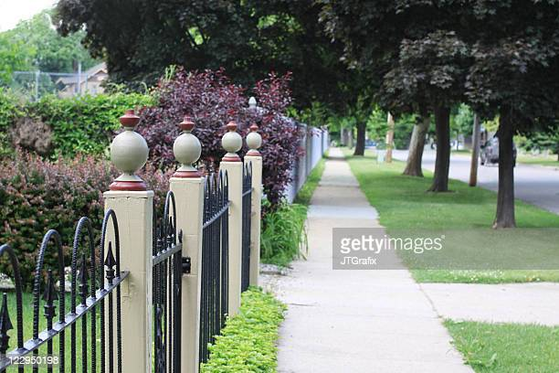 neighborhood sidewalk with fence posts - kalamazoo stock pictures, royalty-free photos & images