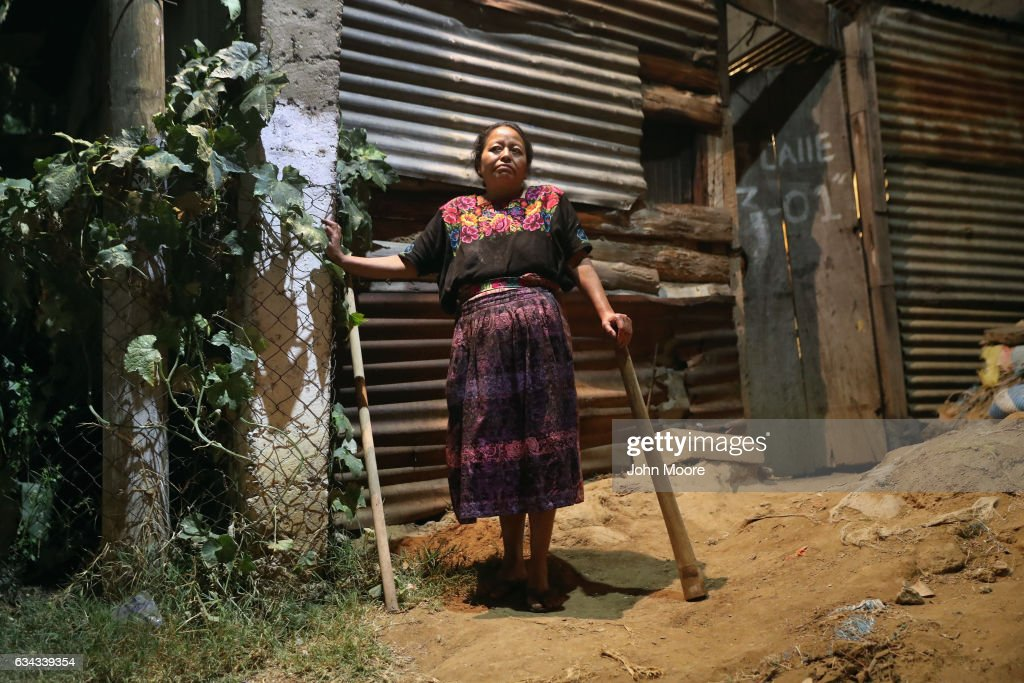A neighborhood watch volunteer stands guard outside her tortilla business on February 9, 2017 in Peronia, Guatemala. Residents of Peronia, south of Guatemala City organized to secure their community after ten of their neighbors were killed in January, they say, for refusing to pay extortion money to gangs. Armed with machetes and sticks, residents take turns each night, baring strangers' entry into their neighborhoods. Violence and poverty continue to drive emigration from Central America to the United States, even as the Trump administration moves to tighten border security.
