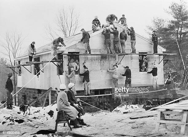 Neighborly Buildup Wilbraham Massachusetts Sitting on a sawhorse Mrs Harry Harvey and her daughter Francis watch workmen build their new home The...