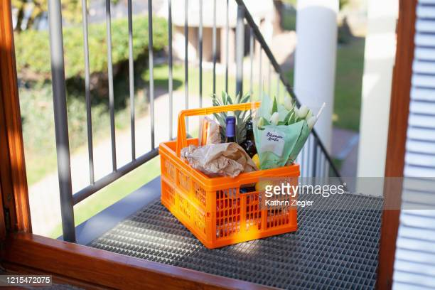 neighborly help: a basket full of groceries left at the door - 外出禁止令 ストックフォトと画像