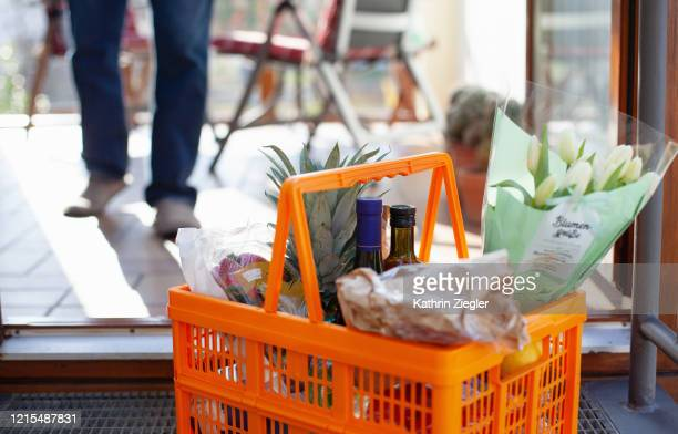 neighborly help: a basket full of groceries left at the door - food delivery stock pictures, royalty-free photos & images