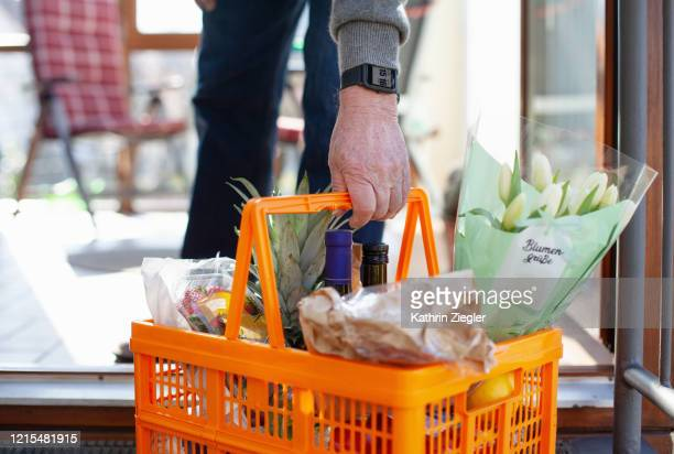 neighborly help: senior man bringing in a basket full of groceries that was left at the door - stay home - fotografias e filmes do acervo