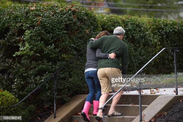 Neighbors around the corner from the site of a mass shooting at the Tree of Life Synagogue embrace one another in the Squirrel Hill neighborhood on...
