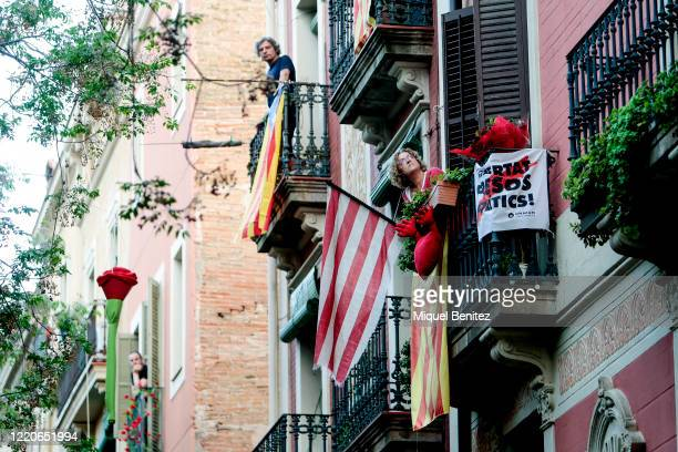 Neighbors celebrate on their decorated balconies with flags and red roses during Sant Jordi, Saint George's Day at Gracia neighborhood on April 23,...