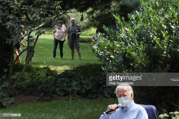Neighbors look from the yard next door as Democratic presidential nominee Joe Biden meets with veterans and union leaders in the backyard of a...