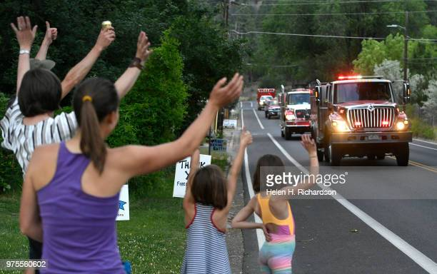 Neighbors Sandy Gilpin left Sandhya Tillotson and Gilpin's twin daughters Tava in stripes and Analee in shorts wave at firefighters during shift...