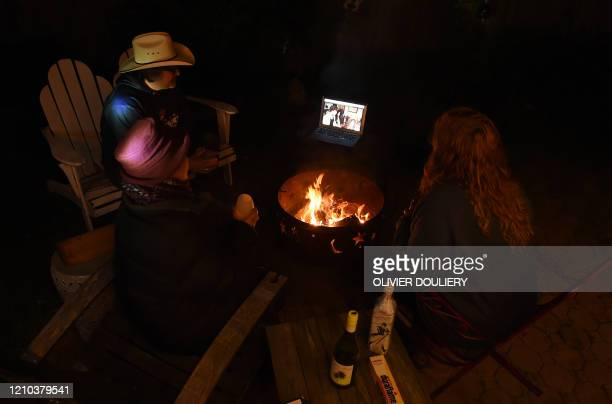 "Neighbors sit around a fire-pit to watch Shawn Mendes and Camila Cabello perform during the ""One World: Together at Home"" concert in a backyard on..."