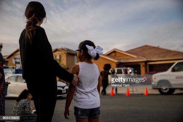 Neighbors stand outside the day after a Perris husband and wife are in custody on suspicion of torture and child abuse at a home on 100 Block of Muir...