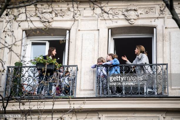 Neighbors talk to each other from their balconies in Paris, on March 19 as a strict lockdown comes into effect to stop the spread of the COVID-19 in...