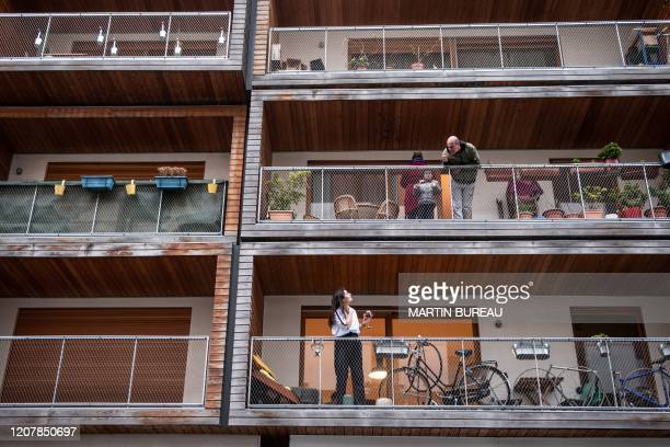 Neighbors talk to each other from their balconies in Paris, on March 20 as a strict lockdown comes into effect to stop the spread of the COVID-19 in...