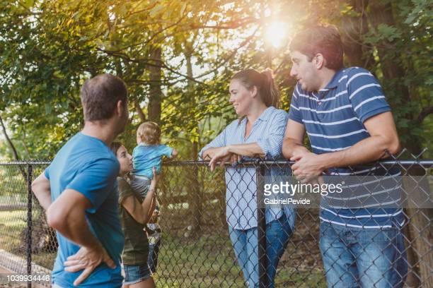 隣人がフェンスとの間の話 - 隣人 ストックフォトと画像