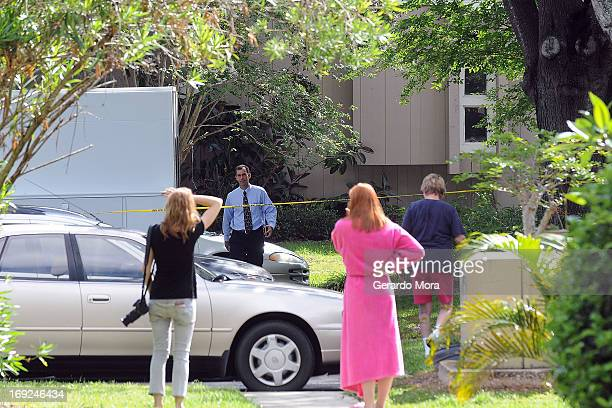 Neighbors watch a Federal Bureau of Investigation evidence response team work outside an apartment where a suspected friend of the Boston bombers was...