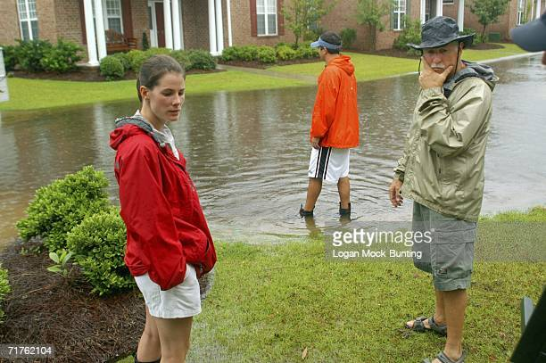 Neighbors watch the waters rise as Tropical Storm Ernesto approaches August 31 2006 in Wilmington North Carolina Ernesto picked up speed in the warm...