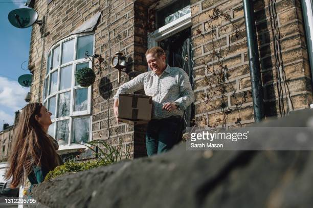 neighbour dropping off parcel - positive emotion stock pictures, royalty-free photos & images