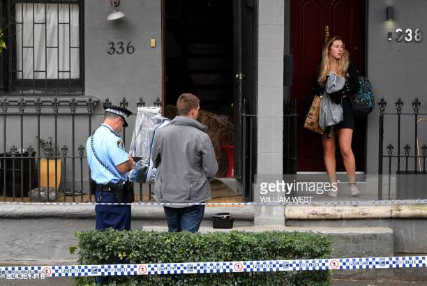A neighbour leaves as police stand guard outside a house in the inner Sydney suburb of Surry Hills on July 30 after it was raided in a major joint...