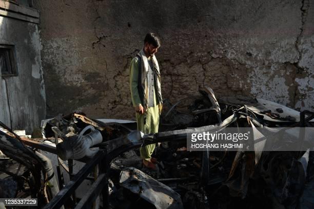 Neighbour of Ezmarai Ahmadi, stands amid the debris of Ahmadi's house that was damaged in a US drone strike in the Kwaja Burga neighbourhood of Kabul...