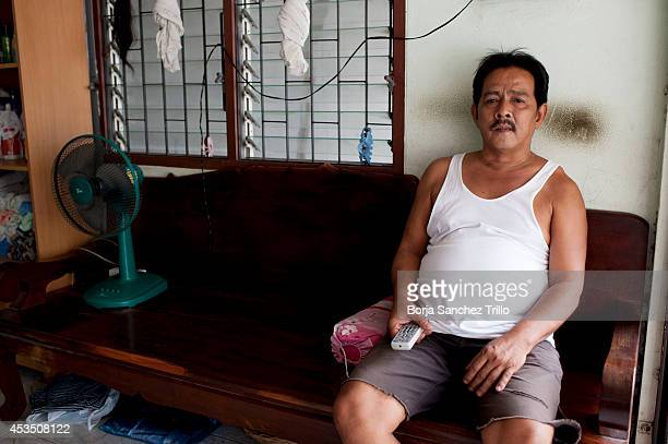 A neighbour poses for a photo inside his shop which is beside the parents house of Thai surrogate mother Pattaramon Chanbua where she used to work on...
