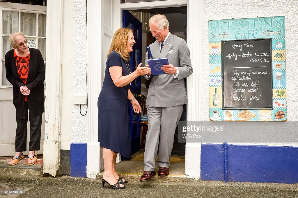 A neighbour watches as Jill Stein presents Prince Charles, Prince of Wales with a bottle of wine and a book commemorating 40 years of Rick Stein's seafood restaurant during his visit to Padstow on July 20, 2015 in Cornwall, England.