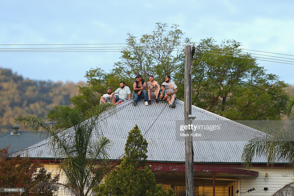 Neighbouring residents watch the match from the roof of their house across the road from the ground during the NSW Origin match between City and Country at Scully Park on May 8, 2016 in Tamworth, Australia.