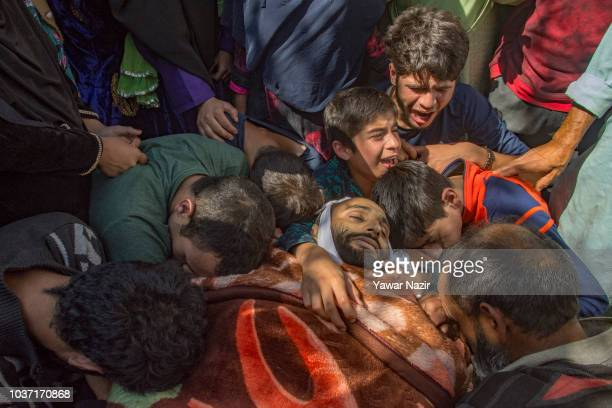 Neighbours and relatives of Firdous Ahmad an Indian policeman killed by suspected militants mourn around his body during his funeral on September 21...