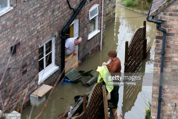 Neighbours chat outside their flooded homes after the River Severn burst it's banks on February 26, 2020 in Ironbridge, England. Shrewsbury,...