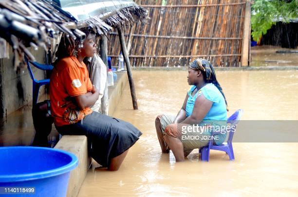 Neighbours chat while sitting in a flooded street of the Paquite district of Pemba on April 29 as Cyclone Kenneth hit northern Mozambique, killing 38...