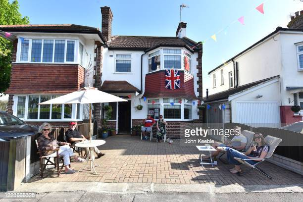 Neighbours keep their social distance on the driveway while enjoying a VE day street party on May 08, 2020 in Leigh on Sea, England. The UK...