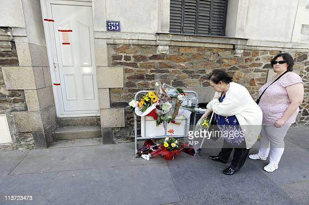 Neighbours lay flowers at the foot of a metal barrier placed outside Dupont de Ligonnes' family home on April 23 2011 in French western city of...