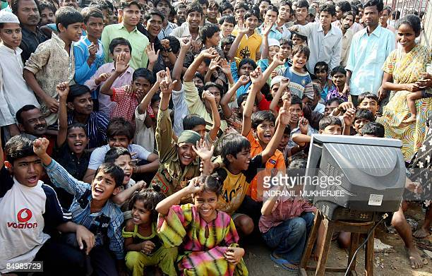 Neighbours of 'Slumdog Millionaire' child actor Mohammed Azharuddin cheer as they watch the Oscars on television in Mumbai on February 23 2009 India...