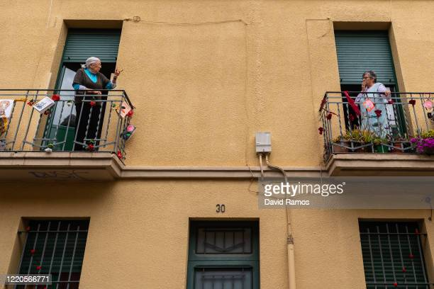 Neighbours speak from their decorated balconies with red roses during Sant Jordi Day on April 23, 2020 in El Prat del Llobregat, Spain. Catalans are...