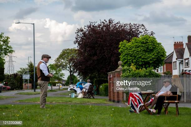 Neighbours speak to each other from outside their homes during a socially distanced street party for VE Day on May 8 2020 in Bulkington United...