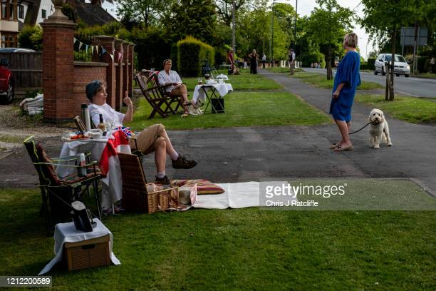 Neighbours speak to each otter from outside their homes during a socially distanced street party for VE Day on May 8, 2020 in Bulkington, United...