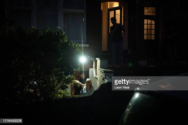 Neighbours stand on their doorsteps as they join in with the applause on April 02 2020 in London United Kingdom Members of the public are being...
