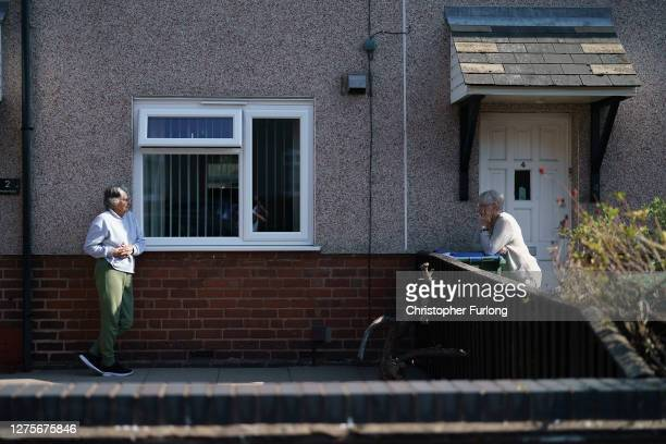 Neighbours take part in a socially distant chat over the garden fence in Tipton on September 22, 2020 in West Bromwich, United Kingdom. Since easing...