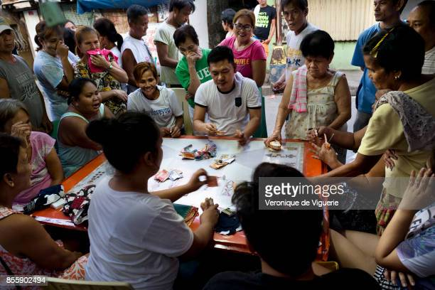 Neignbourgs are betting and playing cards in front of Flor John's house The money made will help with the funeral services Flor John drug user was...