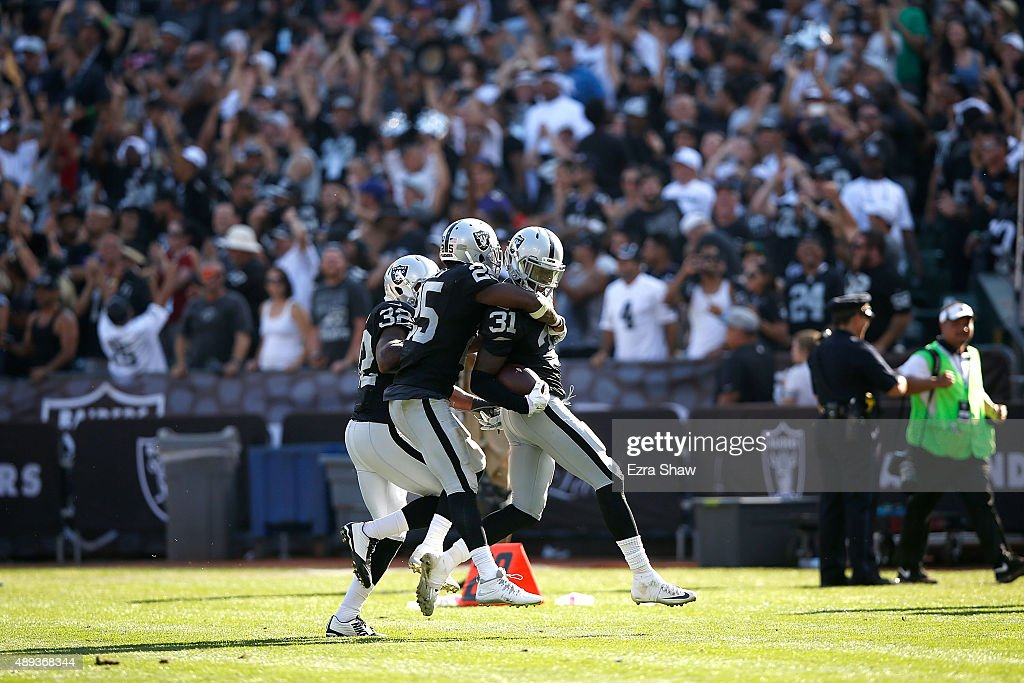 Neiko Thorpe #31 of the Oakland Raiders celebrates an interception in the fourth quarter with teammates Keenan Lambert #32 of the Oakland Raiders and D.J. Hayden #25 of the Oakland Raiders against the Baltimore Ravens at Oakland-Alameda County Coliseum on September 20, 2015 in Oakland, California.