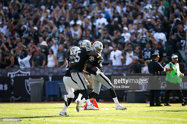 Neiko Thorpe of the Oakland Raiders celebrates an interception in the fourth quarter with teammates Keenan Lambert of the Oakland Raiders and D.J....