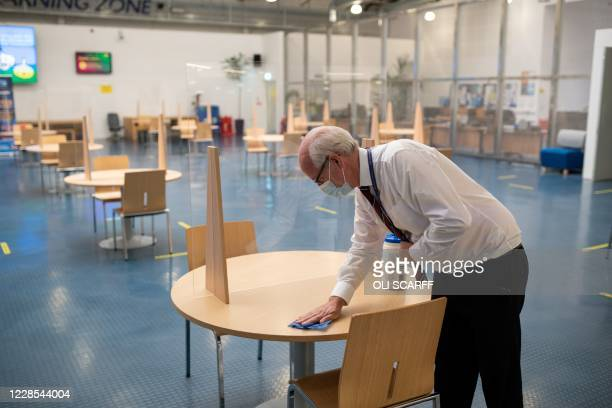 Neil Berry, a Facilities Manager at the University of Bolton, cleans a communal workspace with socially distanced seating and perspex screens on...