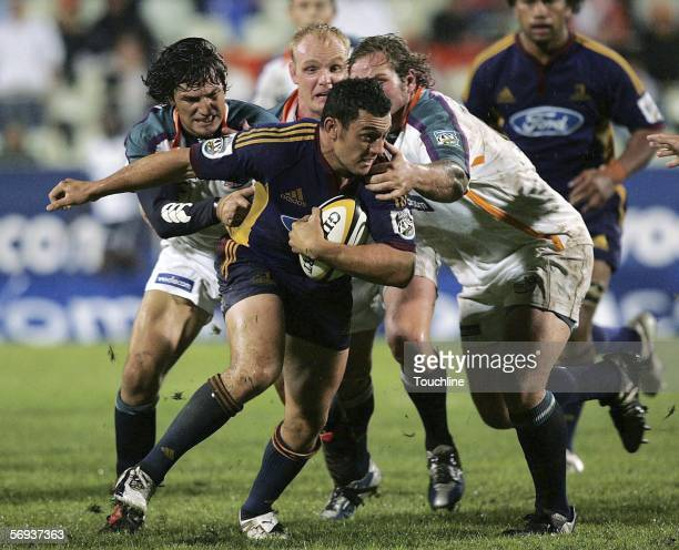Neil Brew of the Highlanders is tackled by Gaffie du Toit and Jannie du Plessis of the Cheetahs during the Super 14 match between the Vodacom...